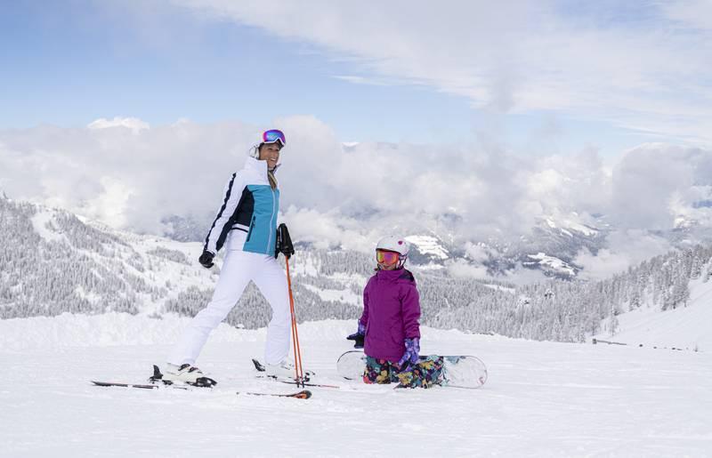 """<p>Ein Kind auf einem Snowboard auf Knien vor einer Frau auf Skiern. Die Skipiste ist perfekt präpariert und die Landschaft rundherum tief verschneit. Der Himmel ist blau nur über dem Tal sind ein paar Wolken zu sehen. Dieses Bild entstand im Skigebiet Nassfeld in Kärnten, dem Skigebiet an der Grenze zu Italien, welches auch zu den """"TOP 10 Skigebieten"""" Österreichs gehört.</p>"""