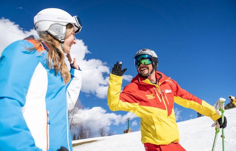 Skilehrer klatscht mit Schülerin ab